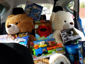 Back seat filled with toys and games, including two very large teddy bears seated as if they were passengers, Star Wars Game, Elmo
